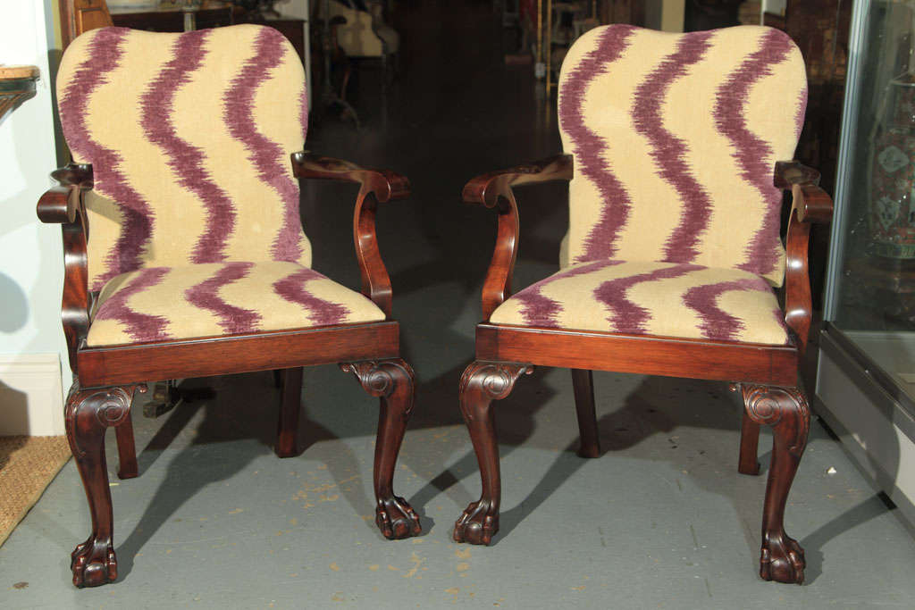 A pair of English bench made, newly upholsted mahogany open armchairs with carved legs ending on ball and claw feet.