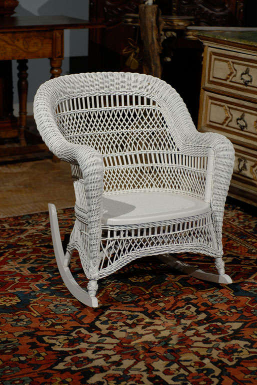 A wonderful wicker rocking chair with arms and an arched back.