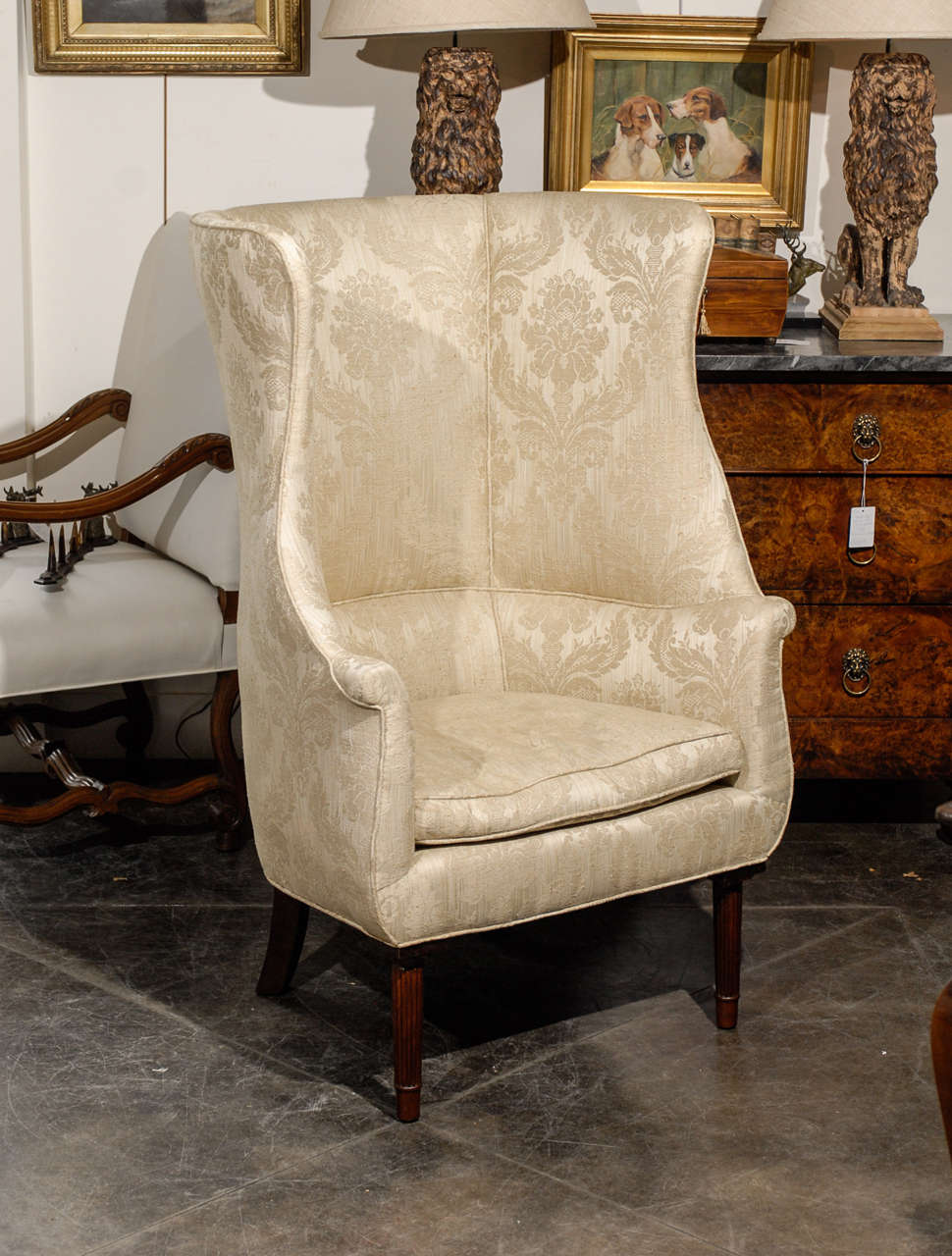 Unknown 1920s Large Barrel Back Upholstered Wing Chair Raised On Four Reeded Legs For
