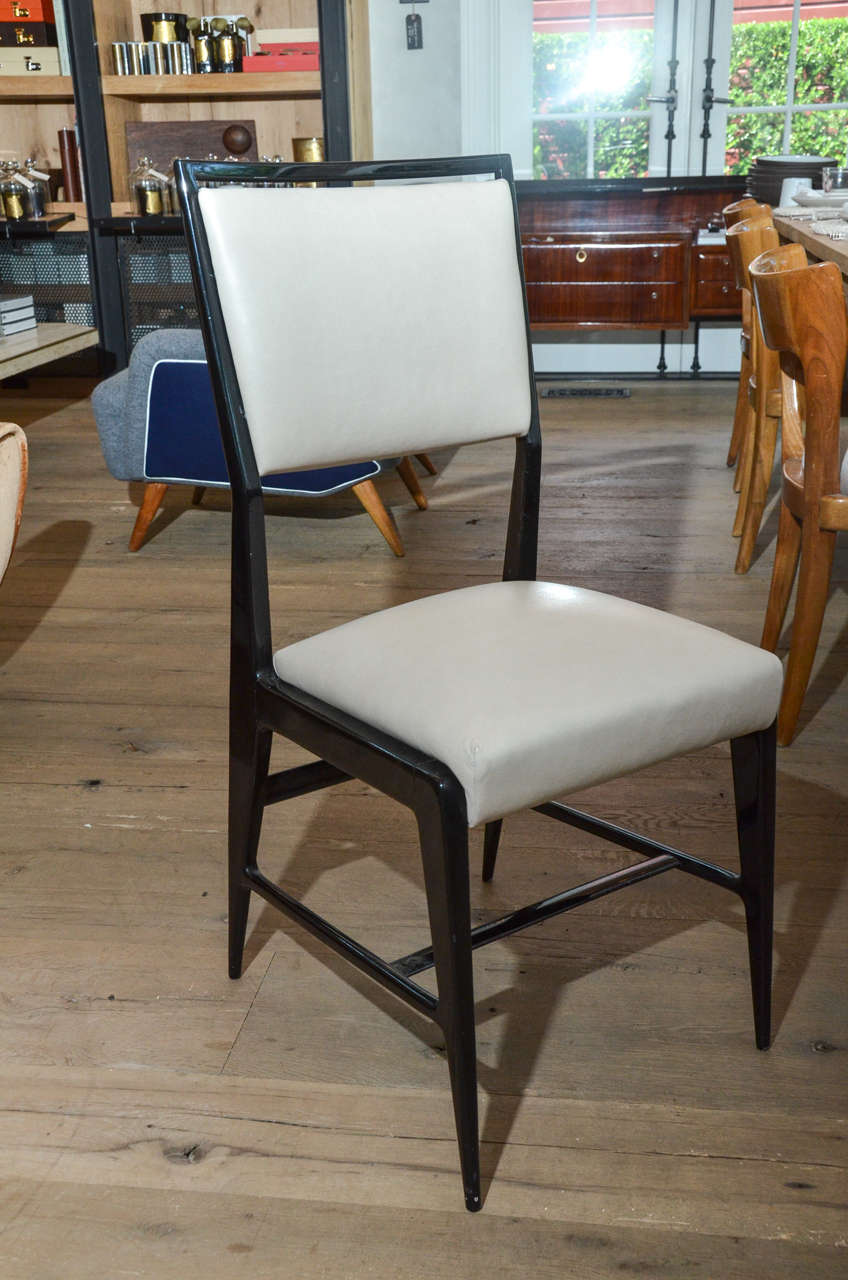 Stunning pair of occasional chairs attributed to Gio Ponti newly re-upholstered in oyster color calfskin leather contrasting beautifully with the black color frame and legs.