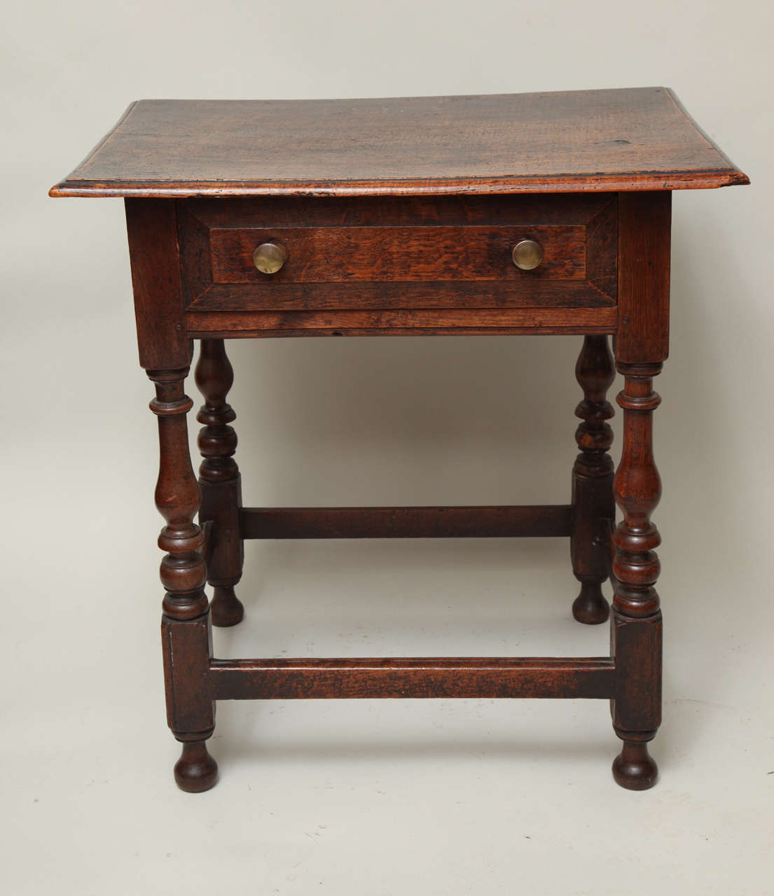 Very good late 17th century English ash and oak side table, the single plank tiger ash top with thumb molded edge, over single drawer with chamfered edge, over boldly turned balustrade legs with beaded edge and original bun feet, joined by beaded