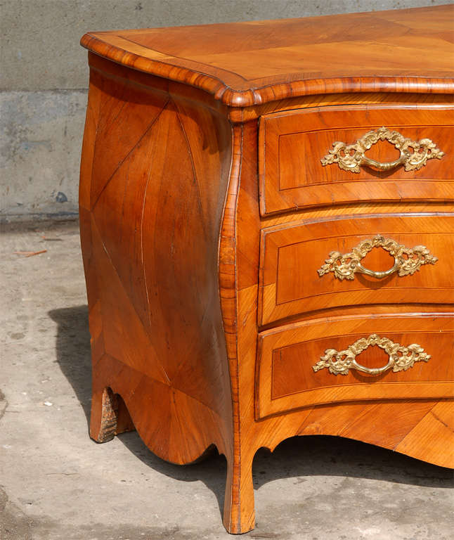 An 18th century Swedish period Rococo Serpentine three-drawer chest with elm veneer and gilt hardware. This Swedish chest features an interestingly shaped deeply scalloped skirt and sits on slight cabriole feet. This piece would be a lovely touch to