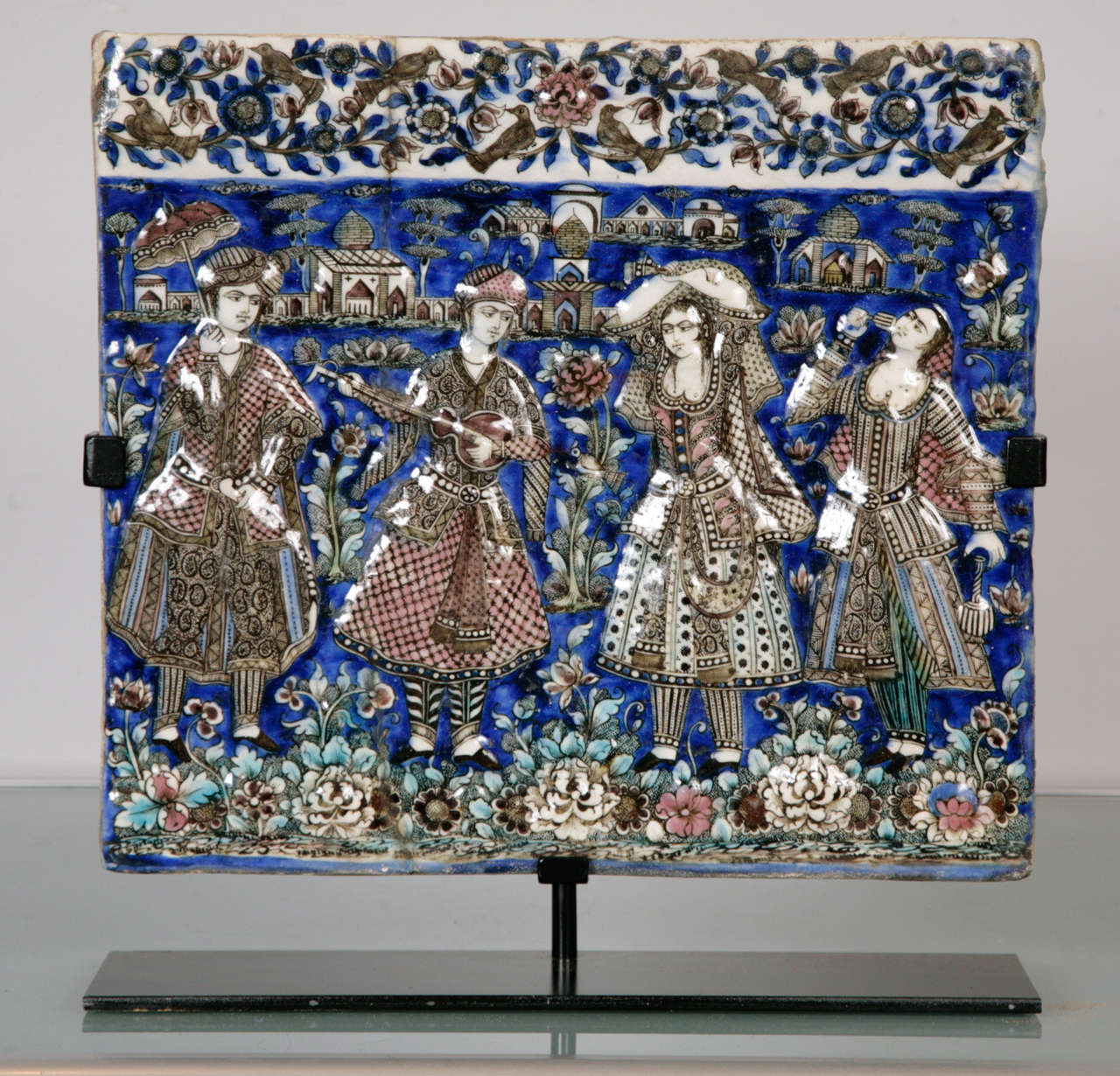 A polychrome tile moulded in relief, the scene depicting musicians and dancers. The figures depicted are dressed in Qajar court costume; the far left figure seen holding a parasol. The musicians are standing in front of a landscape with various
