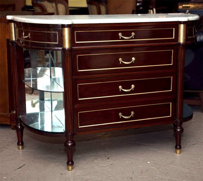 French Directoire style bow-front server, circa 1930s, the white half-moon marble atop a narrow frieze fitted with three drawers, over a three-drawer chest flanked by mirror-back glass shelvings on each side, raised on bulbous legs ending in brass