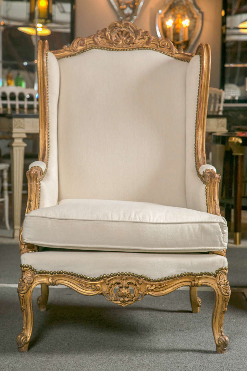 Pair of vintage grand French Louis XV style wingback bergere chairs, circa 1930s with later upholstery and brass studs, beautiful distressed gilded frame decorated with elegant carvings of seashell, scrolls, and acanthus motifs, padded back leading