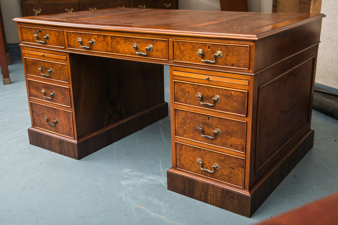 A three-piece, tan leather surface with tooling and gilding is the starting point for this three part pedestal desk in walnut burl. Classic touches abound in the appearance and construction of this handsome desk. A nod to modern desk use includes a