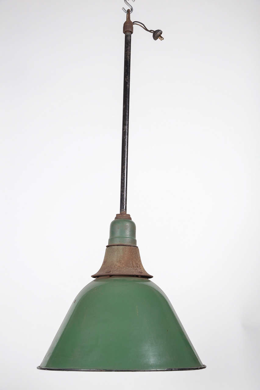 These industrial lights are medium large scale with an original green enamel finish. Salvaged from an old foundry in Birdsboro, Pennsylvania. Accepts Mogul base bulbs but can be retrofitted to accept standard bulbs with an inexpensive adapter.