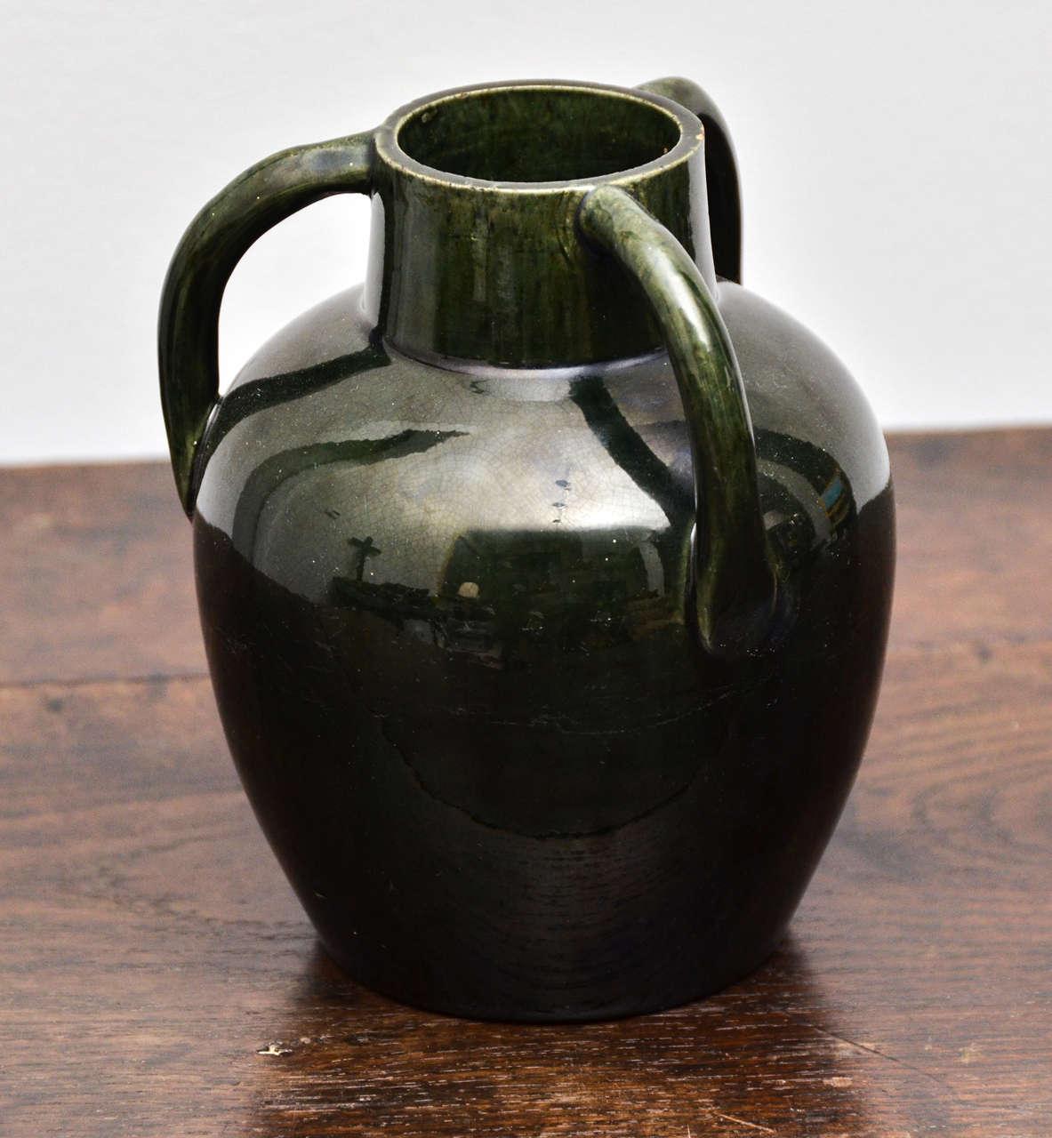 Dark green ceramic jug with high gloss glazing and three handles.