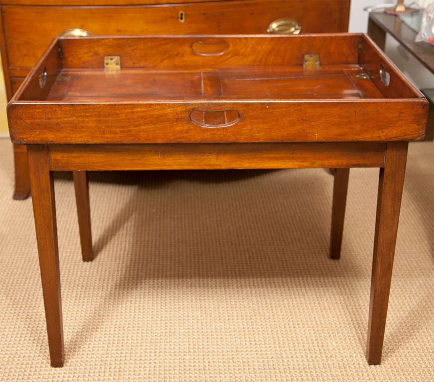 A Georgian solid mahogany folding butlers tray with brass hardware on a later mahogany stand.