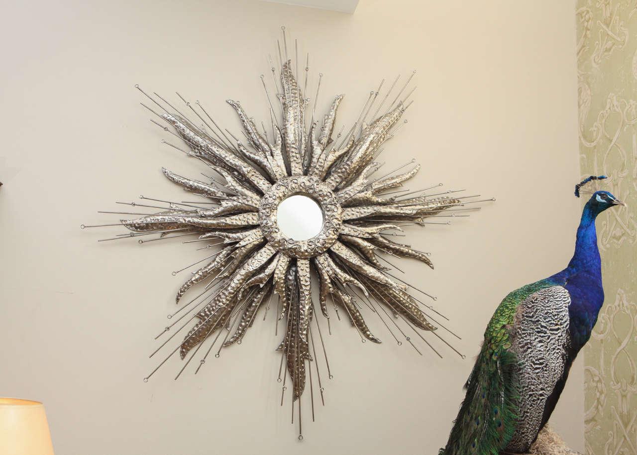 Large hammered silvered metal starburst with center mirror.