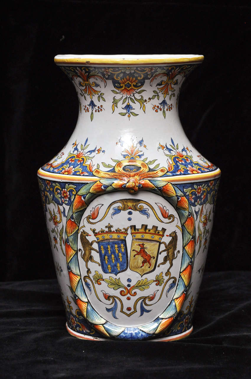 An extraordinary pair of French faience vases hand-painted in the luxurious, polychrome, opaque tin glazes that made Rouen faience so famous. The delicate paisley pattern begins at the very top of the vase and continues down to the base, interrupted