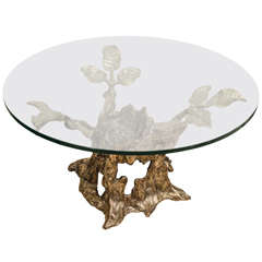 Circular glass top side table with rustic tree form bronze base
