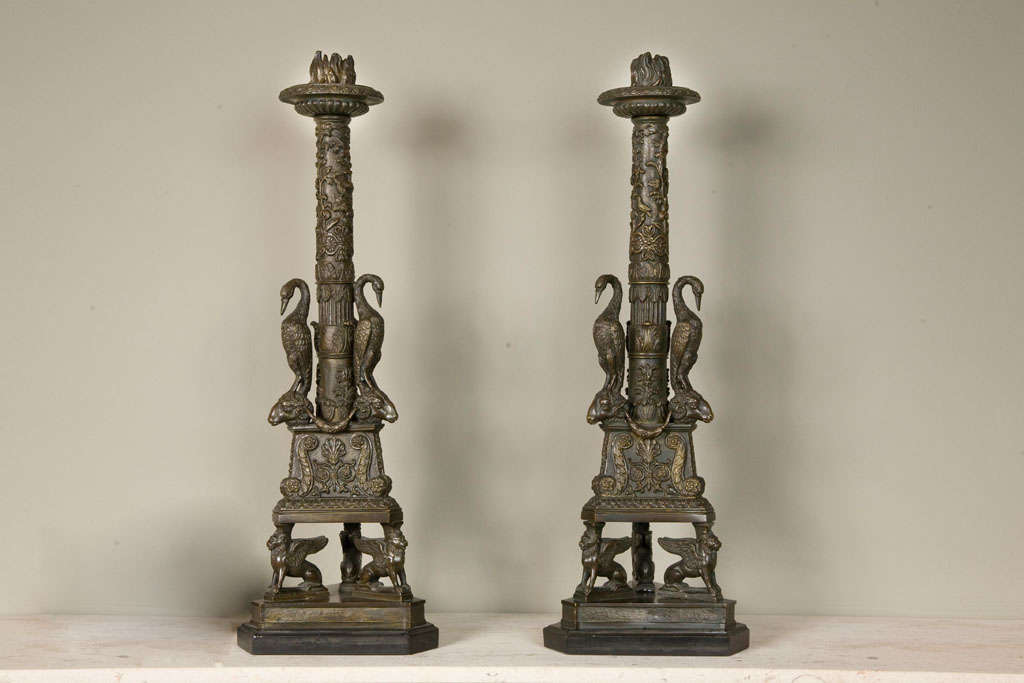 A pair of gilt bronze candlesticks of neo-classical form, probably English, 19th century, after a design by Giovanni Battista Piranesi and similar to the Newdigate candelabrum in the collection of the Ashmolean Museum, the columns with three cast