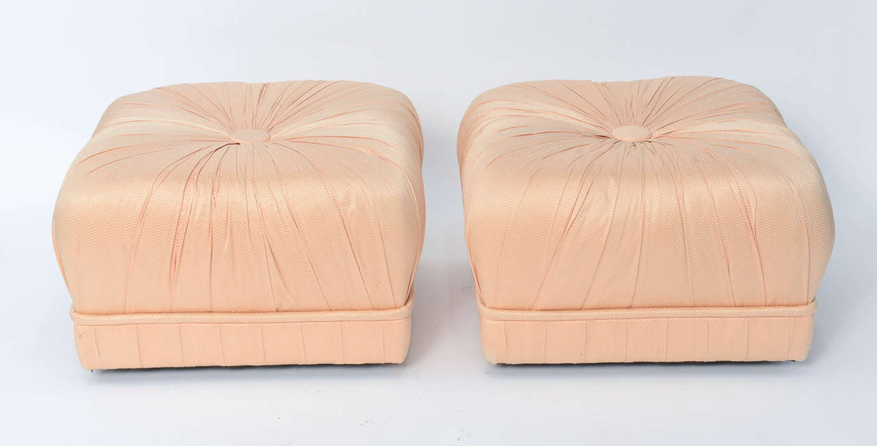 Glamorous and luxe, this pair of Hollywood inspired poufs is dramatic with their heavily pleated styling and large centre tuft, a souffle style. Original fabric in good order with a couple of light signs of age. On casters and easily movable, they