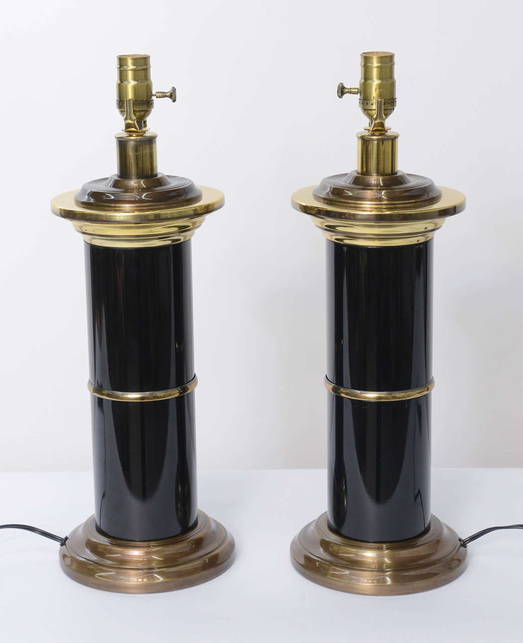 Quite elegant and sleek, strong and masculine, this pair of modern Empire style table lamps has a wonderful fat column of black lacquered brass with stepped circular base, centre brass belt and column capital of multi-stepped brass. Rich and with a
