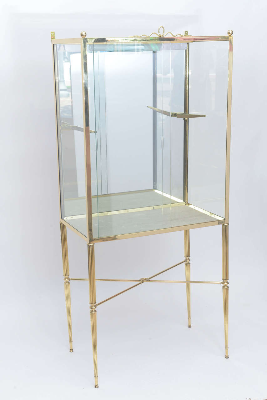 Beautifully designed display cabinet in brass and glass with adjustable single shelf not shown very much in the manner of Osvaldo Borsani. Illuminates from above.