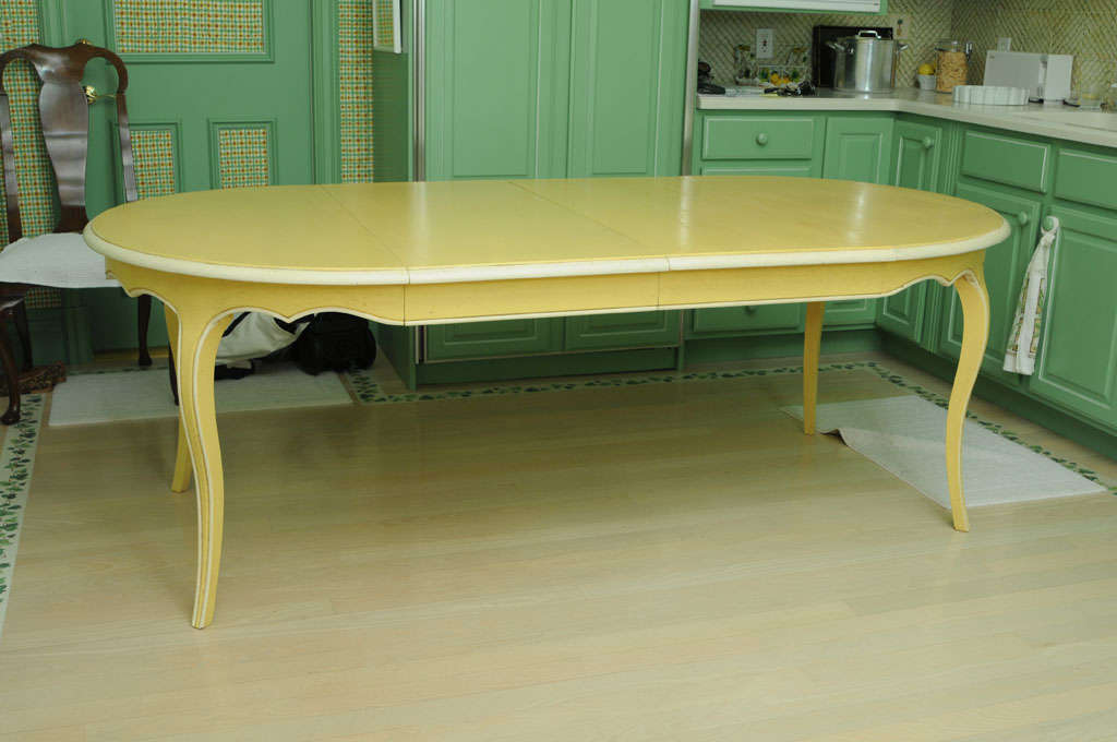 Famous French Furniture Manufacturer DE TONGE distressed painted massive oak dining table round or oval with 2 leaves in a provencal yellow with creamy white detailing. Round 44.5