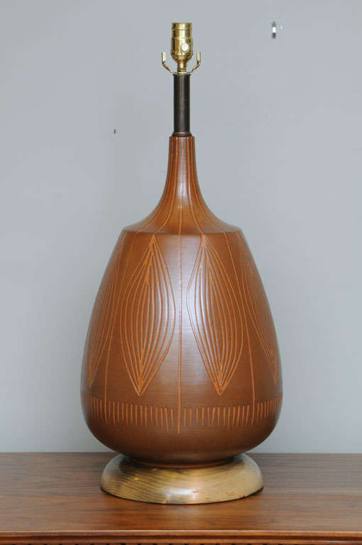 Wonderfully organic in form with a Sgraffito design on the surface of ti leaves or cacoa pods, this large Mid-Century table lamp was created by George Nobuyuki Kimura and offered by his firm, Sy Allan Designs of California. A large bulbous form, it