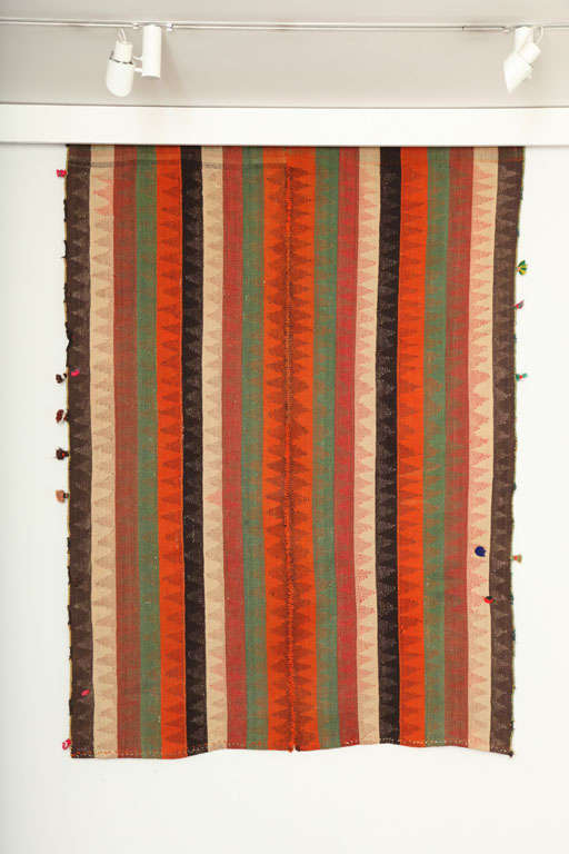 This 1920 Persian Jajim with decorative poms was created using organic vegetable dyes and pure handspun wool. It is an improvisational piece intended for a variety of uses by the weaver: as a blanket, a sofreh and of course as decoration in her