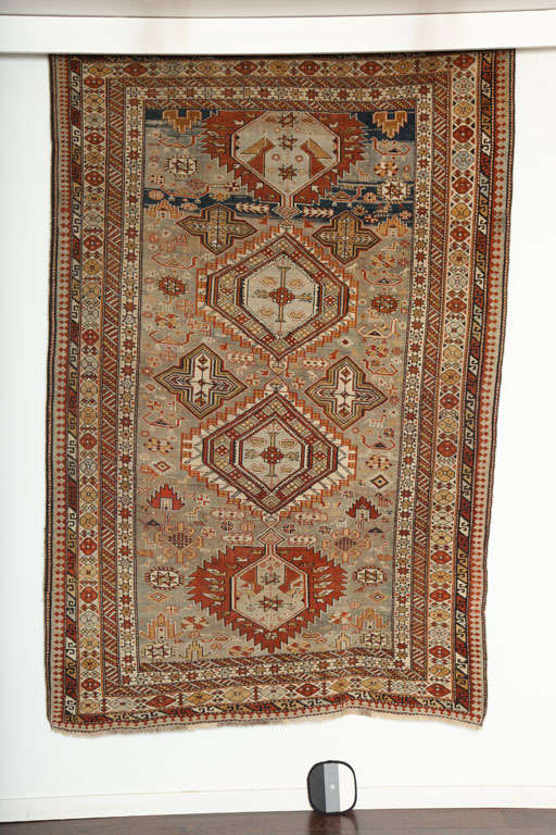 This 1880s Shirvan rug consists of a handspun wool warp, weft and pile and its soft yet rich blues, reds and golds were all created using organic vegetable dyes. The coloration of this carpet is truly unique and exceptional for a piece of its age