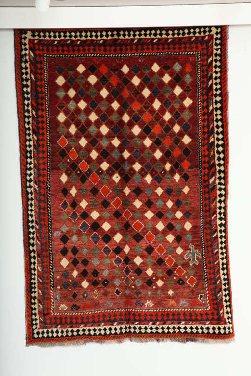 This 1930 Persian Gabbeh rug consists of a handspun wool warp, weft and hand-knotted pile. Its rich reds, greens and blues were all created using natural vegetable dyes; and the creams, browns and blacks exhibit the beautiful natural coloration of