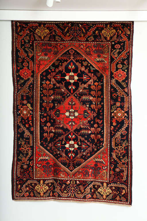 This 1900-1910 Persian Mishan Malayer rug consists of a cotton thread warp, handspun wool weft and hand-knotted handspun wool pile. Its rich reds, coppers, midnight blues and golds were all created using organic vegetable dyes. Woven in the village