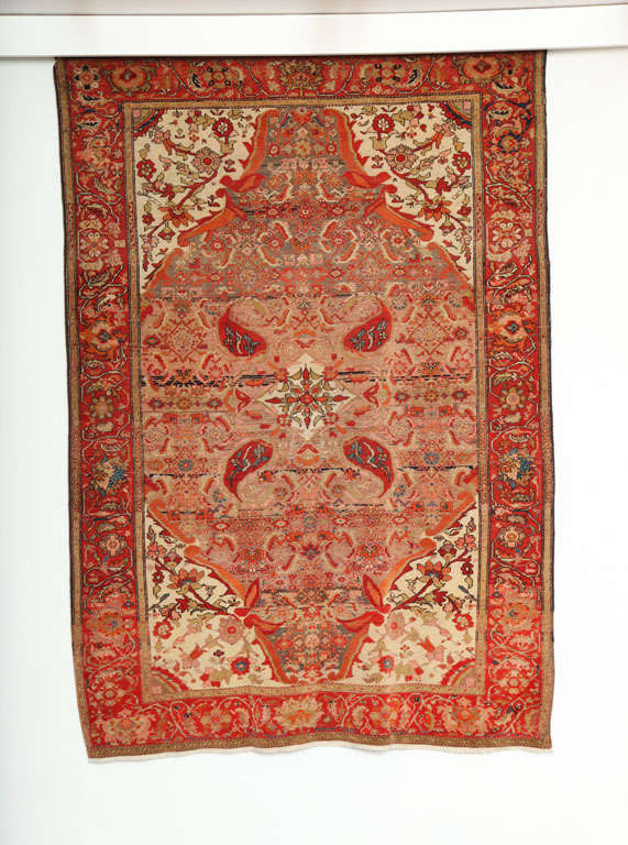 This 1870-1880 Persian Mishan Malayer rug consists of a cotton warp, handspun wool weft and hand-knotted handspun wool pile. Its vivid reds, oranges, pinks, and blues were all created using organic vegetable dyes. The cream, gold and taupe tones