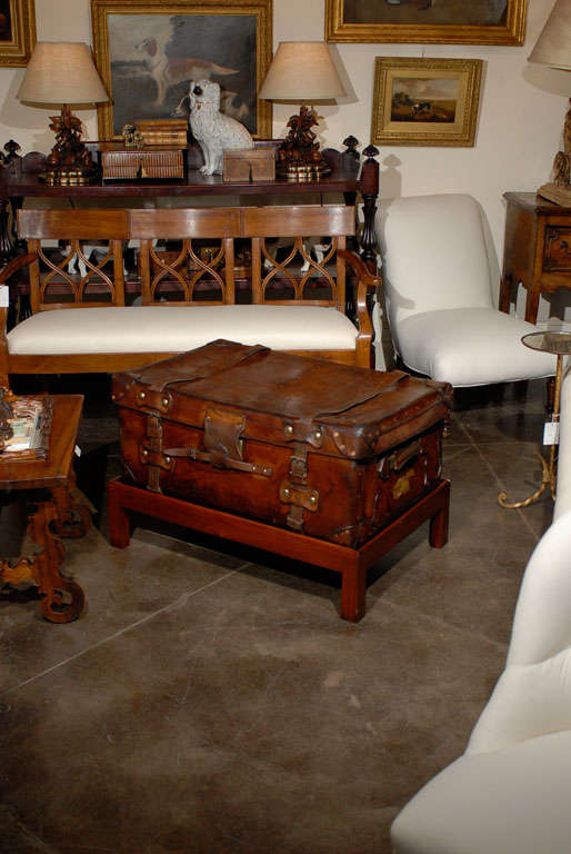 An English leather trunk on custom stand made into a coffee table. This English trunk on stand from circa 1880 features a leather travelling case with lateral handles and leather straps raised on a custom rectangular mahogany stand. This well-worn