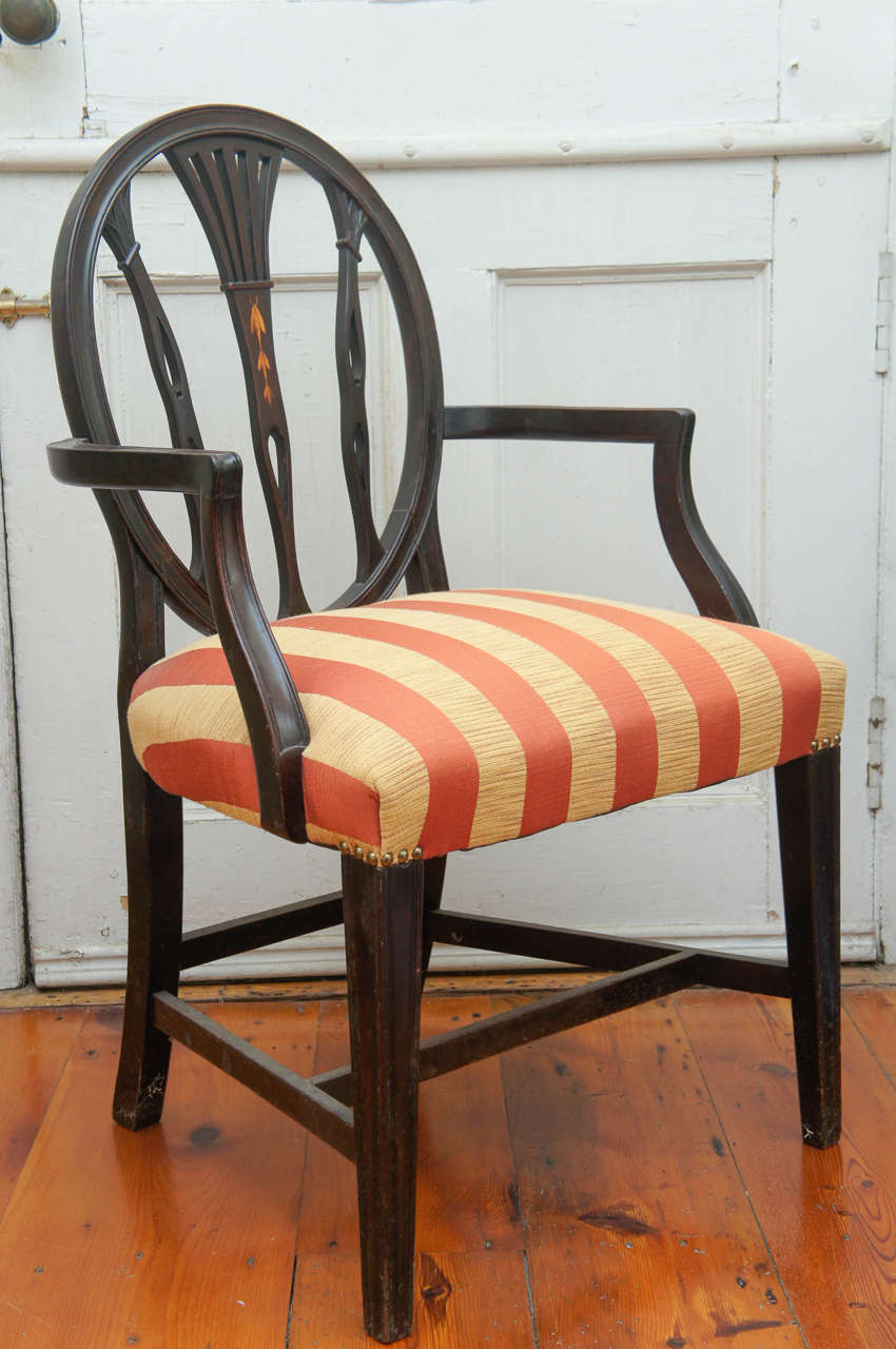 Hepplewhite-style ebonized open-armed chair, circa 1880. Burnished bellflower decoration on back center rail. Quadrille red and yellow striped fabric on tight upholstered seat, finished with upholstery tacks.