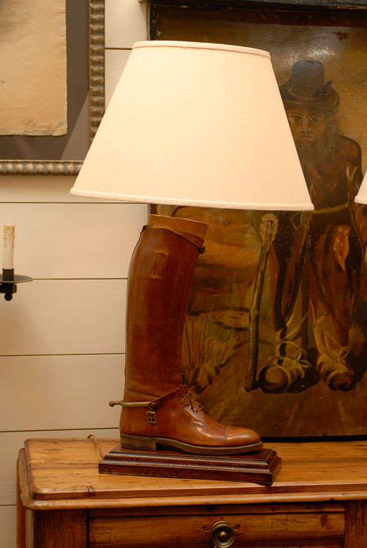This is a pair of English vintage handmade antique brown leather riding boots with their wooden boot trees, mounted and wired as table lamps with cream-colored Empire shades. The left and right boots each presents a nice warm brown color, laces and