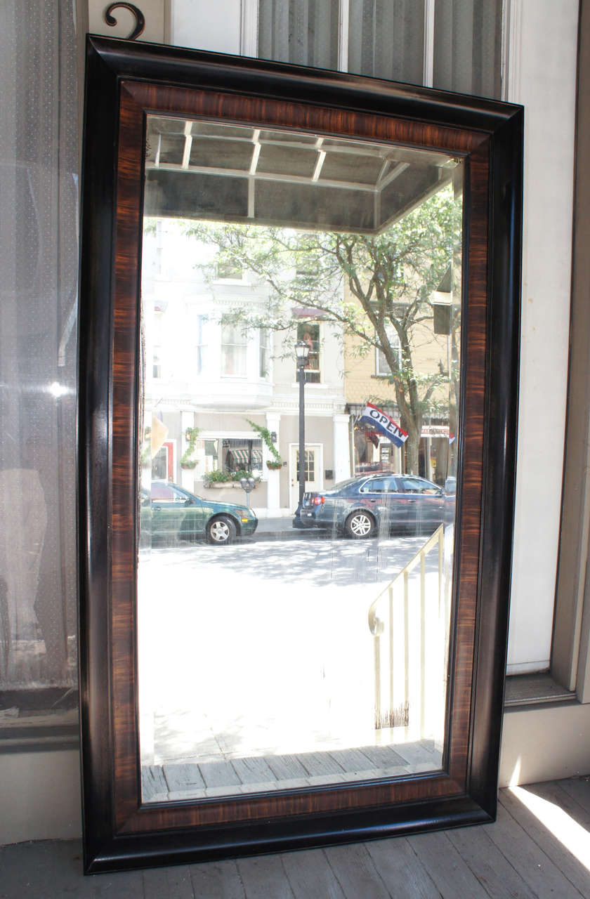 This masculine grain painted mirror frame is composed of two separate frames. The inner frame is grained rosewood in deep long strokes creating a pattern around the mirror and the second outer large and the deeper frame is ebonized and shows some