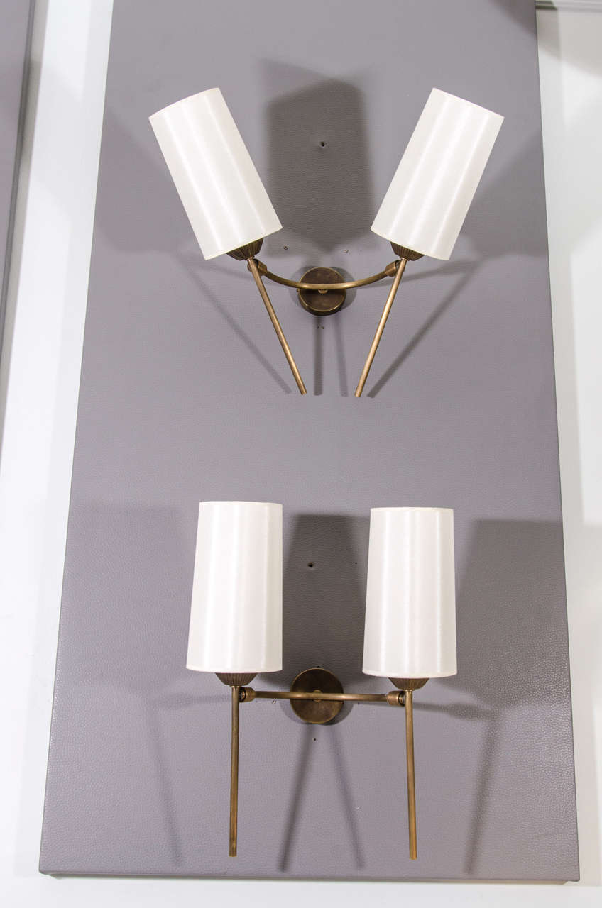 Pair of classically designed French sconces updated with articulations. The sconces can hold a variety of angles and positions. Refinished brass with silk shades.