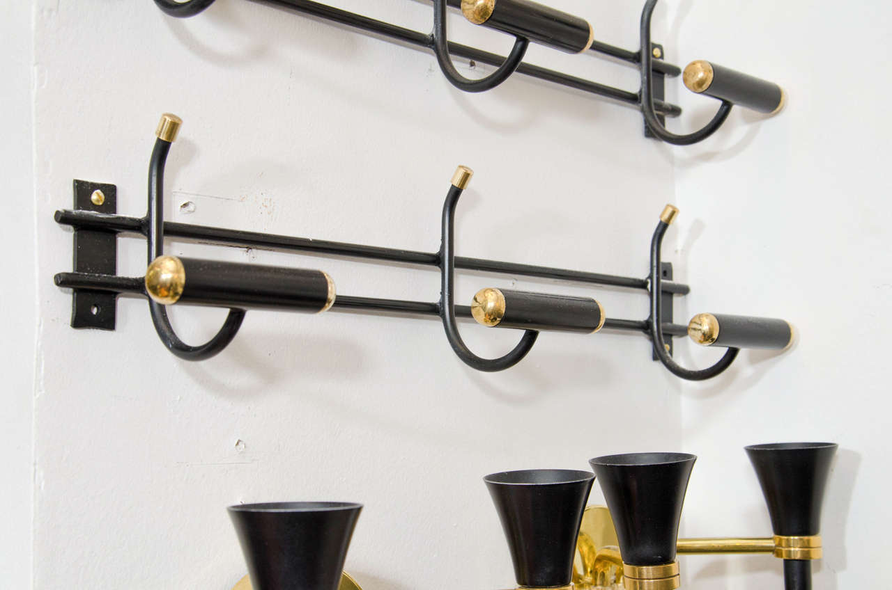 A vintage circa 1950s pair of French rare wall mounted coat racks or Porte-Manteau attributed to Jacques Adnet. Made of black enameled iron with brass accents. Also available individually for $2900