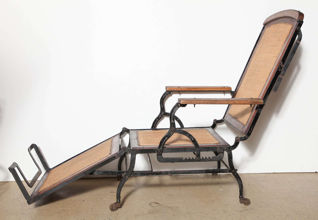 Adjustable Walnut and Black Iron Chaise Lounge Chair designed by Cevedra Sheldon for Marks Adjustable Folding Chair Company of New York. Late 19th Century. Constructed with Black Cast Iron base, frame and legs, Walnut frame, Cane seat, back, leg