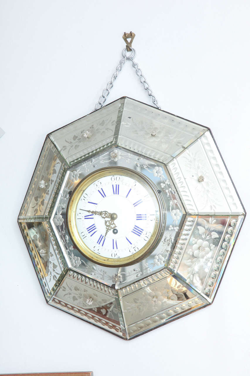 This wonderful clock is set in etched mirrored panels, forming a hexagon. It hangs from a chain.