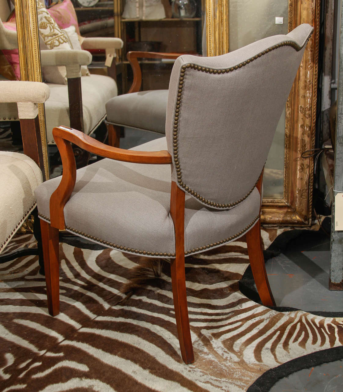 Shield back side chair in grey linen with nailhead trim.
