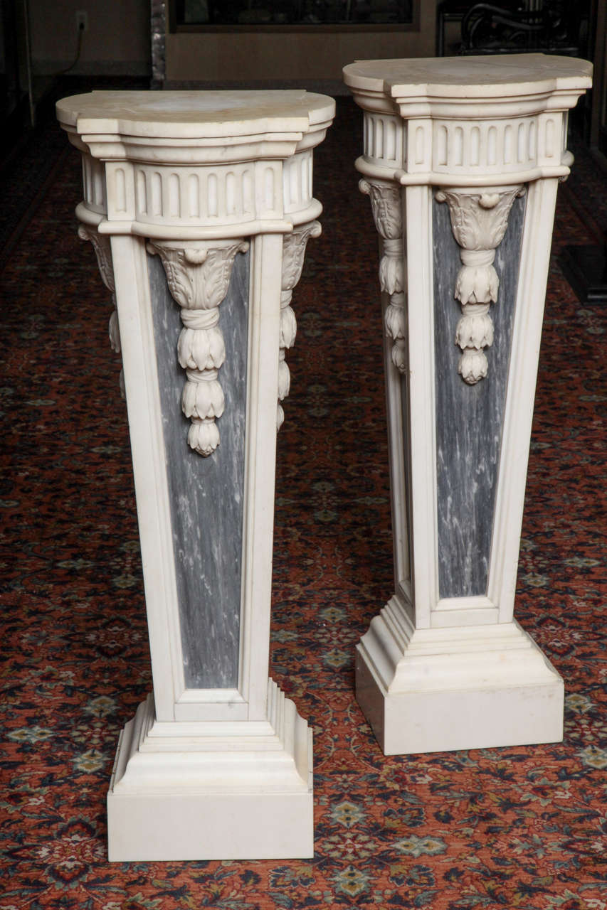 Neoclassical pair of palatial antique French Louis XVI style hand-carved Carrera white and grey marble pedestals of unusual form embellished with raised three dimensional neoclassical motifs, circa 1860s, Paris Measure: Height 122 cm. Top depth