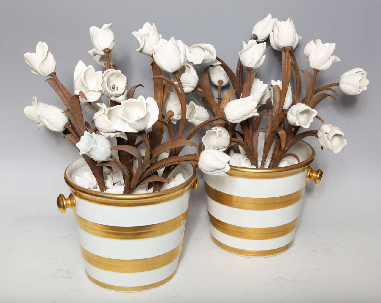 A large and quite unusual pair of antique French Louis XVI style white and gold two handled porcelain buckets filled with white tulips mounted on handmade metal stems, attributed to Jansen Paris, circa 1910.
