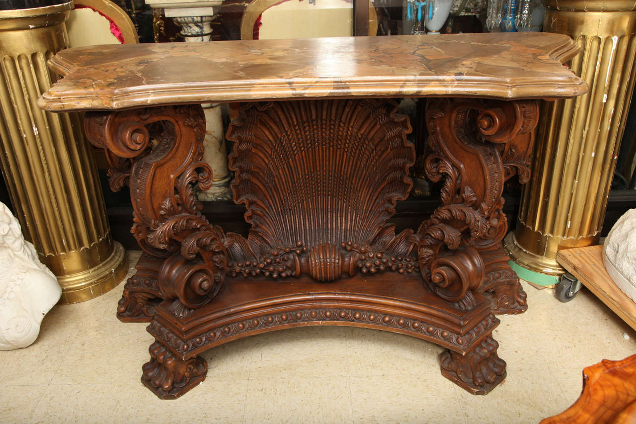 A very fine quality hand-carved Italian Rococo style faux marble top console with shell motif.