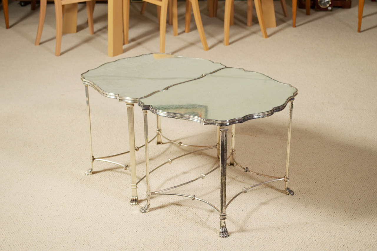 For your consideration is this 1950's pair of silver plated, French plateau, paw footed, neo classical side tables that puzzle piece together to make cocktail table.  The top features antiqued mirrored glass. 