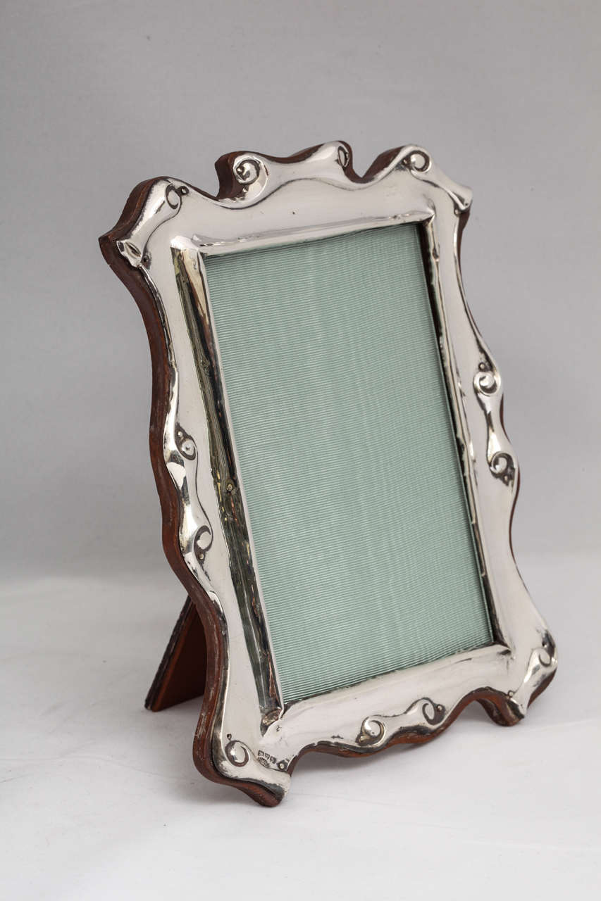 "Edwardian, sterling silver, scroll design picture frame, Chester, England, H. Williamson Ltd. - Maker. Mounted on wood back. Measures: 8 3/4"" high (at highest point) x 5 3/4"" wide (at widest point; shows a 5 1/2"" x 3 1/2"" photo). Excellent condition"