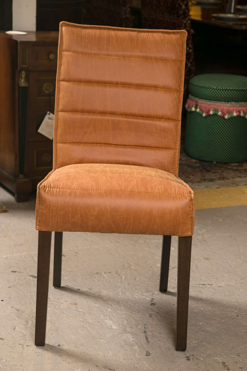 Pair of Hollywood Regency style leather side chairs. Each with a set of mahogany tapering legs supporting a finely padded seat with stitching. The matching backrest having a chrome handle to lift and move.