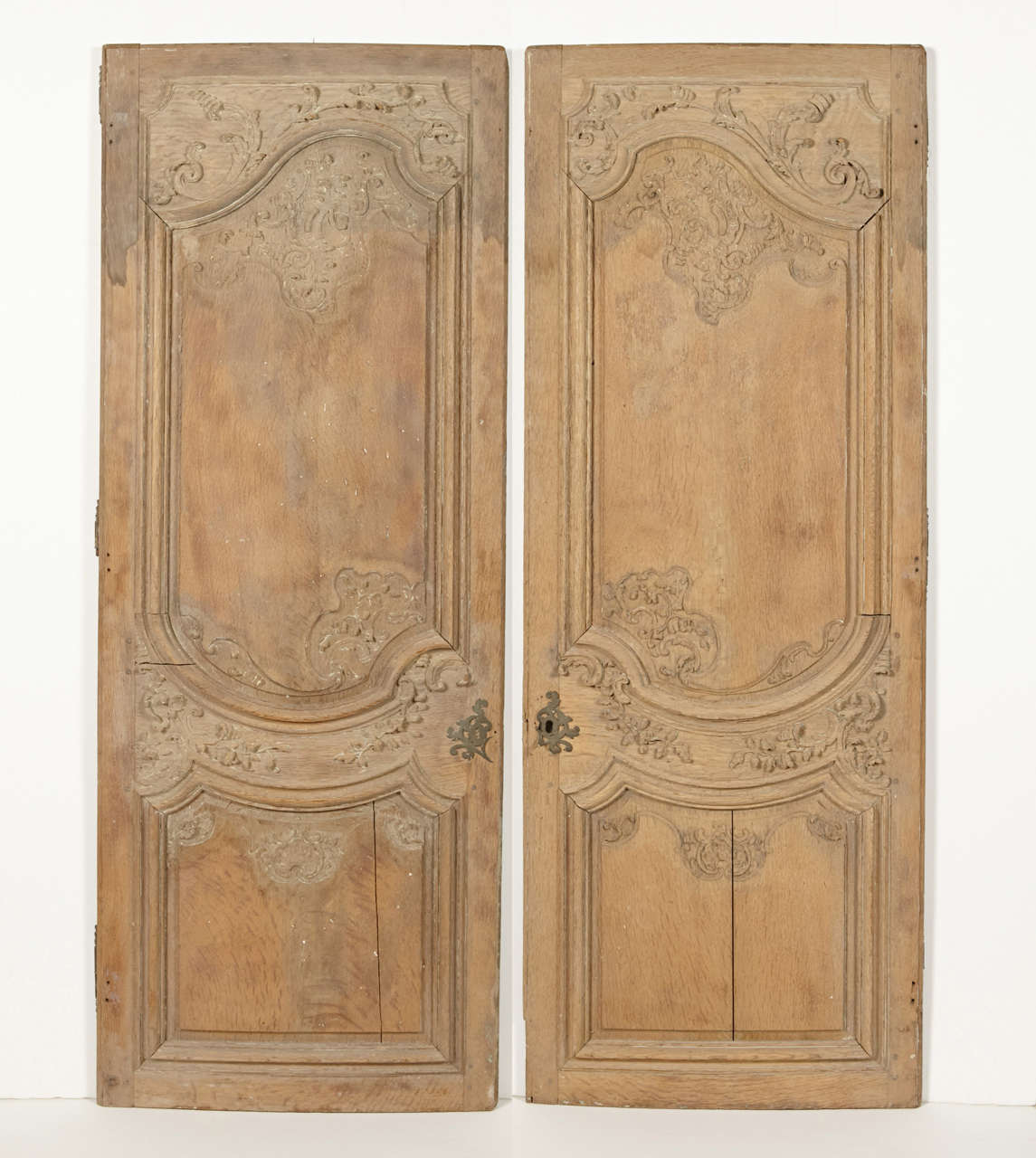 These beautifully hand-carved armoire doors are from the French Regence period (1715-1723). The front sides have been stripped at some point in their history, while the backs are painted in a cream color. Each door has a very subtle bow