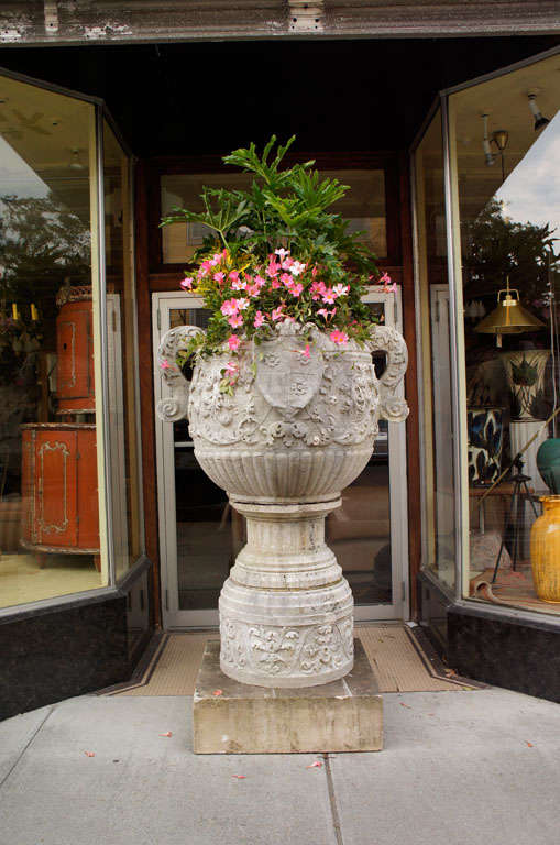 Monumental European urn in limestone with a sandstone base, carved with foliage and birds supporting a crest topped with a fleur-de-lys and quartered with three stylized roses. Possibly French.  The urn is in three sections