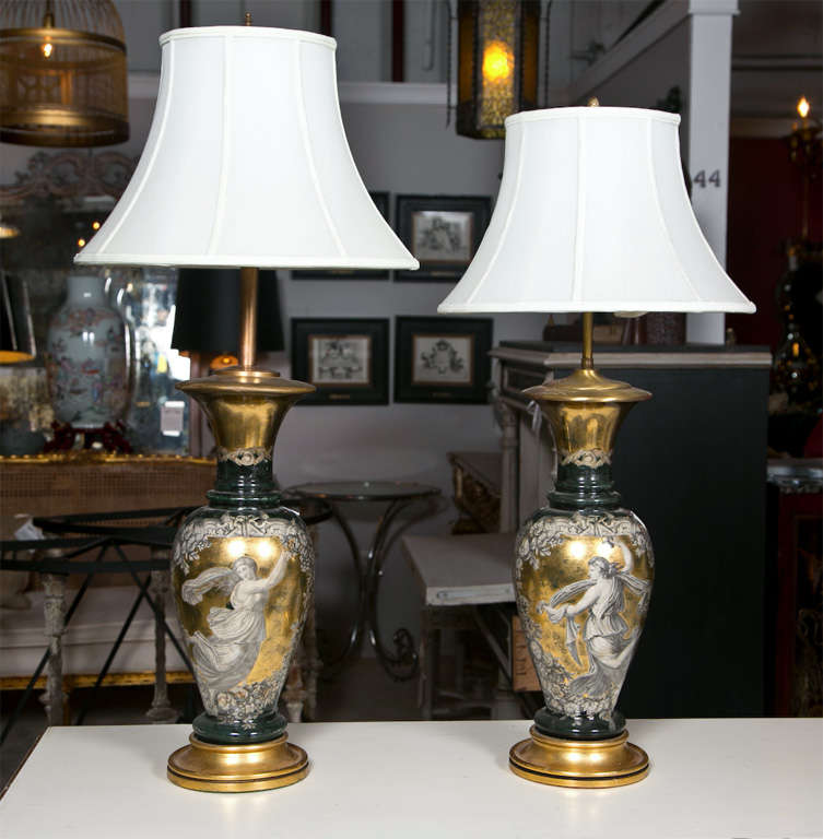 Pair of exceptional Classical style reverse glass table lamps, circa 1940s, urn-shaped form depicting beautiful pattern of goddess on gold-leaf background, supported on circular wooden bases. Shades not included.