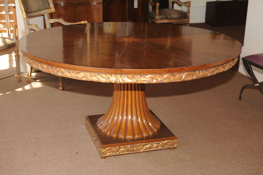 Beautiful hand-carved walnut dining table, the bookmatched veneer top of pie shaped pieces culminating in a fruitwood star, the apron and base elaborately carved with vines and branches which are finished in gold leaf above a fluted splayed pedestal