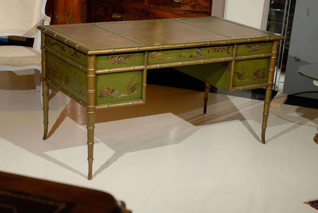 Unique green color faux bamboo chinoiserie vintage desk with embossed leather top over a frieze fitted with three drawers with campaign style handles, supported by two drawers on either side, standing on faux bamboo tapered feet.