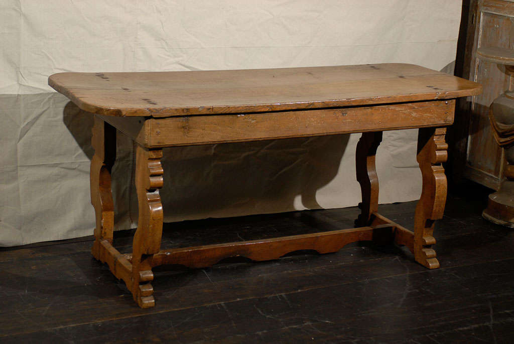 An 18th century Italian trestle base farm table. This Italian chestnut wood farm table features a single plank top, attached to the apron with fabulous old thick nails. The trestle base is made of lyre shaped legs, connected to each other through a