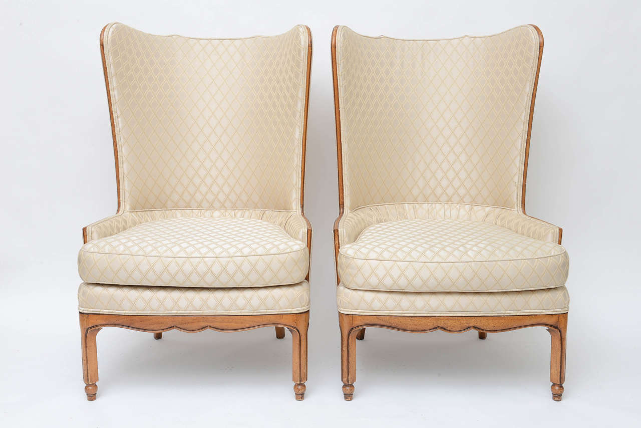 Pair of high back wing tip club chairs, in the manner of Grosfeld house. Original upholstery, crème silk viscose textile with cross-hatched embroidered diamond-shape pattern throughout. Walnut frame, with down-filled seat cushion, tight back seat