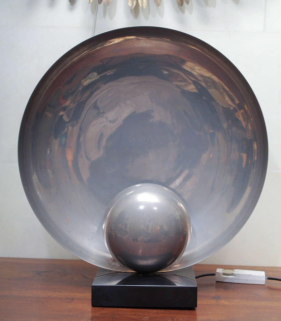 A rare and unusual French Art Deco silver metal moon lamp. The bulb is hidden behind a small silver disc, casting a glowing light on the larger silver disc mounted behind.